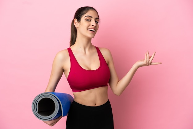 Young sport caucasian woman going to yoga classes while holding a mat extending hands to the side for inviting to come