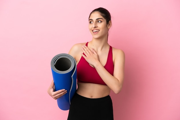 Young sport caucasian woman going to yoga classes while holding a mat looking up while smiling