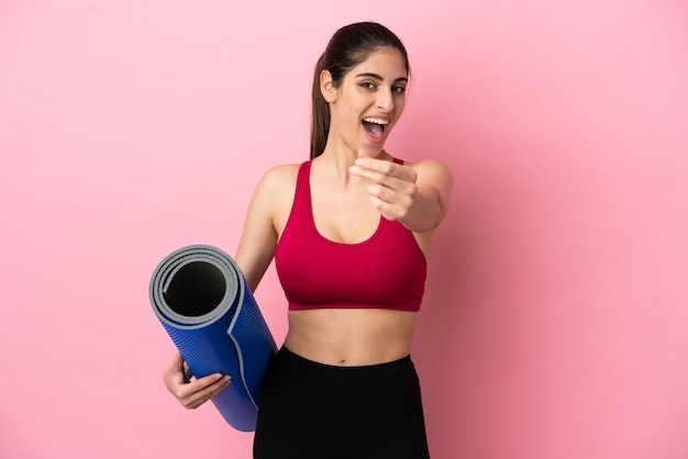 Young sport caucasian woman going to yoga classes while holding a mat making money gesture