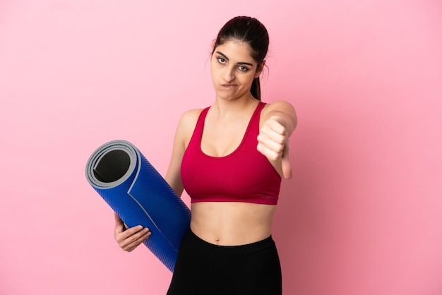 Young sport caucasian woman going to yoga classes while holding a mat showing thumb down with negative expression