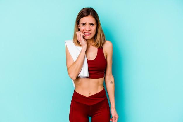 青い噛む指の爪で孤立した若いスポーツ白人女性、神経質で非常に心配しています。