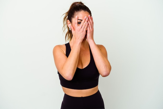 Young sport caucasian woman isolated on white background blink through fingers frightened and nervous.