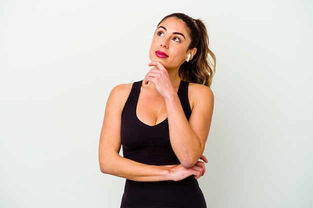 Young sport caucasian woman isolated on white background looking sideways with doubtful and skeptical expression.