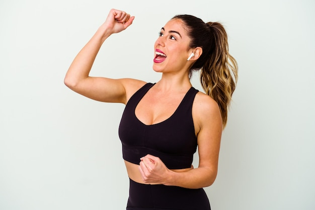 Young sport caucasian woman isolated on white background raising fist after a victory, winner concept.