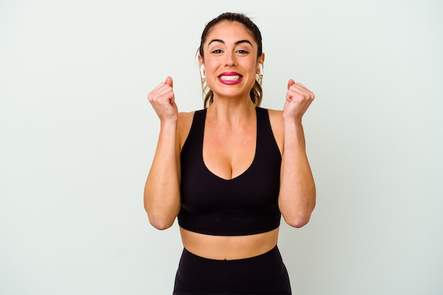 Young sport caucasian woman isolated on white background raising fist, feeling happy and successful. victory concept.