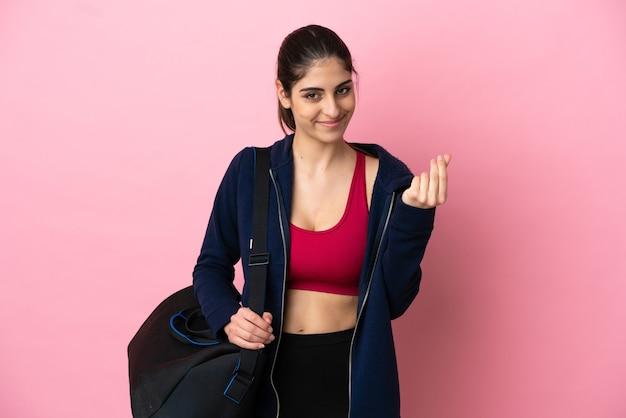 Молодая спортивная кавказская женщина со спортивной сумкой на розовом фоне делает денежный жест