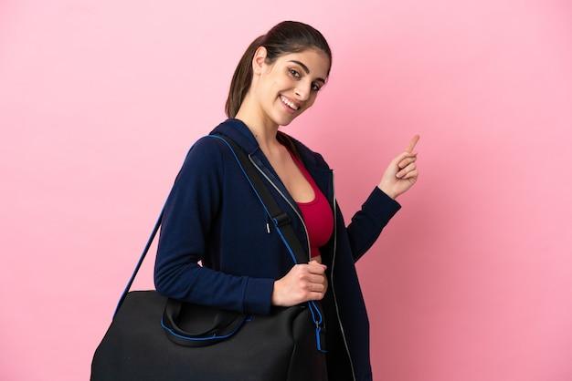 뒤를 가리키는 분홍색 배경에 격리된 스포츠 가방을 든 젊은 스포츠 백인 여성