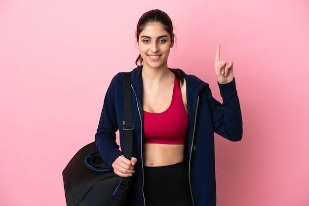 멋진 아이디어를 가리키는 분홍색 배경에 격리된 스포츠 가방을 든 젊은 스포츠 백인 여성