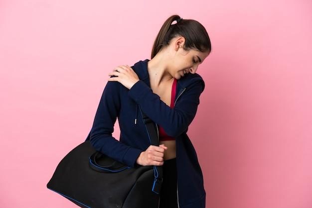 努力したために肩の痛みに苦しんでいるピンクの壁に隔離されたスポーツバッグを持つ若いスポーツ白人女性