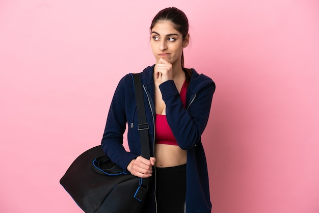 Young sport caucasian woman with sport bag isolated on pink background having doubts and thinking