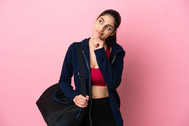 Young sport caucasian woman with sport bag isolated on pink background and looking up