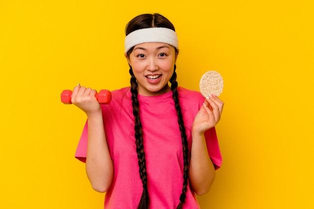 黄色の背景に分離された餅を食べる若いスポーツ中国人女性