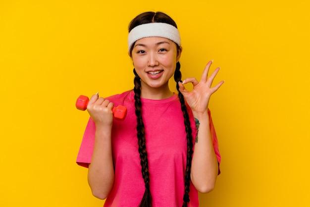 若いスポーツ中国人女性は、黄色の背景に明るく、自信を持ってokのジェスチャーを示しています。
