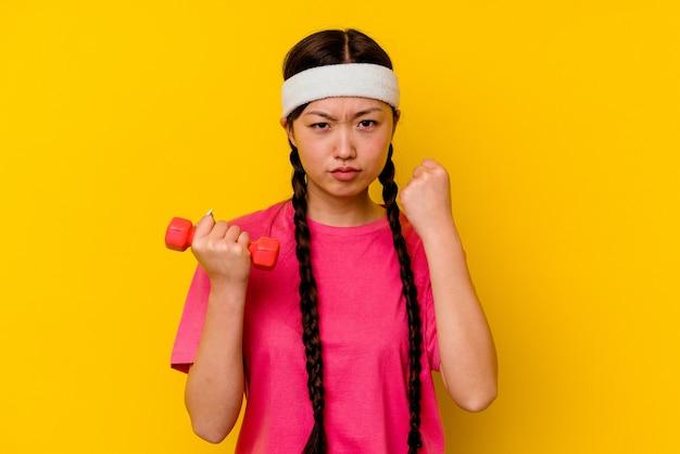 若いスポーツ中国人女性が黄色の背景に分離され、カメラに拳を見せ、攻撃的な表情を見せる。