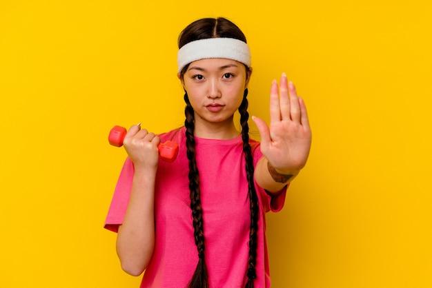 Молодая спортивная китаянка изолирована на желтом фоне, стоя с протянутой рукой, показывая знак остановки, предотвращая вас.