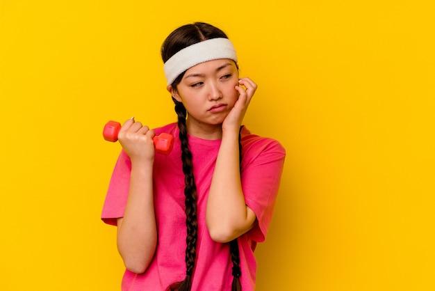 黄色の背景に分離された若いスポーツ中国人女性