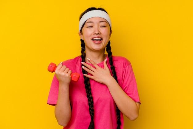黄色で隔離された若いスポーツ中国人女性は胸に手を置いて大声で笑います。