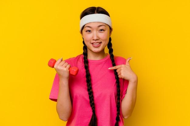シャツのコピースペースを手で指している黄色い人に孤立した若いスポーツ中国人女性、誇りと自信を持って