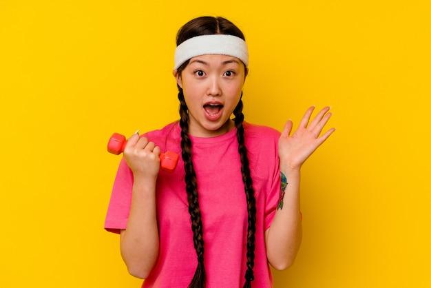 黄色に孤立した若いスポーツ中国人女性は、嬉しい驚きを受け取り、興奮し、手を上げます。