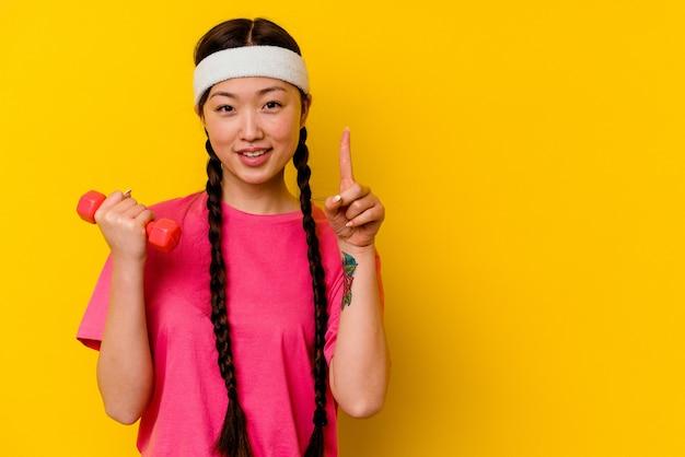 指でナンバーワンを示す黄色で隔離の若いスポーツ中国人女性。