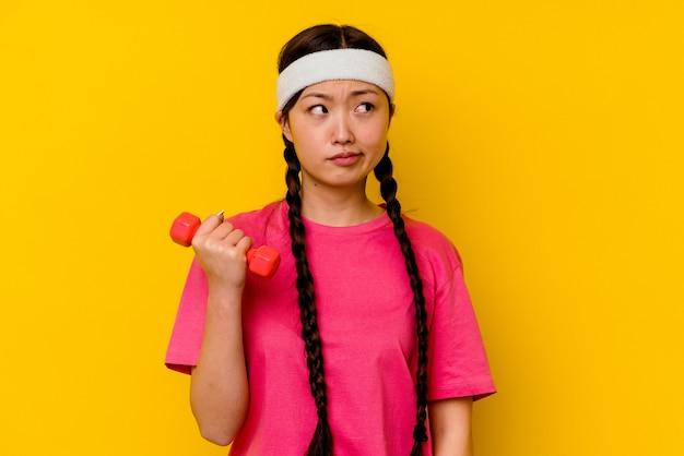黄色の壁に孤立した若いスポーツ中国人女性は混乱し、疑わしく、自信がない