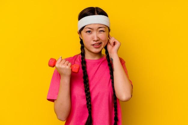 手で耳を覆う黄色の壁に分離された若いスポーツ中国人女性