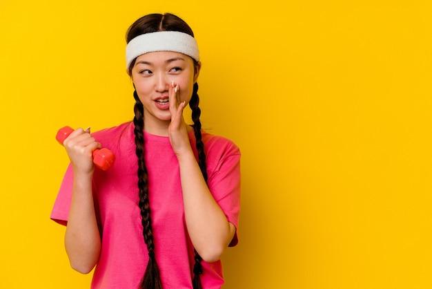 黄色の壁に隔離された若いスポーツ中国人女性は秘密の熱いブレーキングニュースを言って脇を見ています