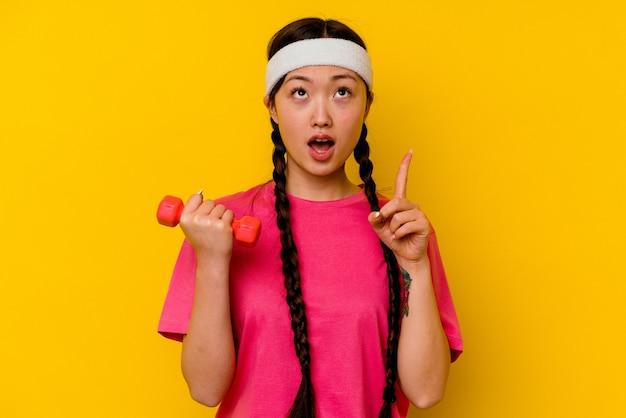開いた口で逆さまを指している黄色の壁に分離された若いスポーツ中国人女性