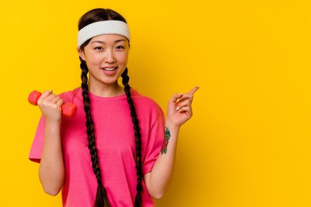 笑顔と脇を指して、空白のスペースで何かを示す黄色の壁に孤立した若いスポーツ中国人女性