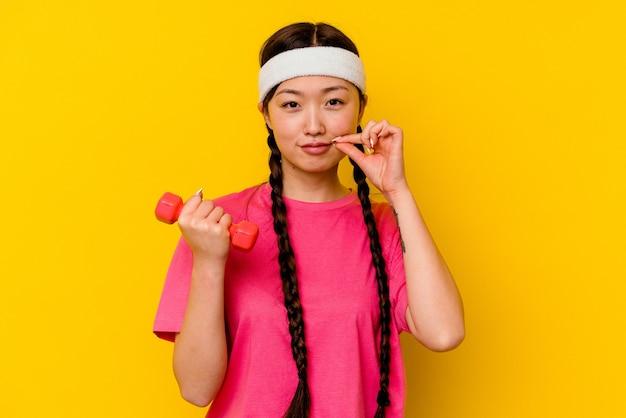 秘密を保持している唇に指で黄色の壁に分離された若いスポーツ中国人女性
