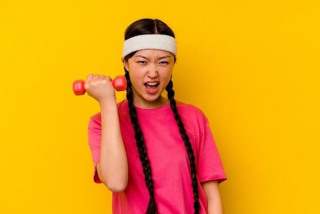 黄色で隔離の若いスポーツ中国人女性