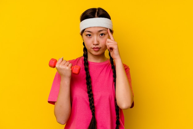 Young sport chinese woman isolated on yellow background pointing temple with finger, thinking, focused on a task.