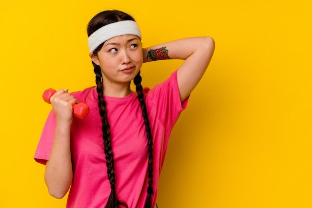 Young sport chinese woman isolated on yellow wall touching back of head, thinking and making a choice.