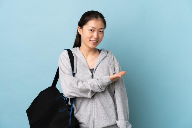 Young sport chinese  woman with sport bag over isolated blue wall presenting an idea while looking smiling towards