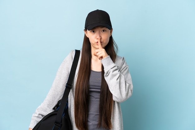 Young sport chinese woman with sport bag over isolated blue wall showing a sign of silence gesture putting finger in mouth