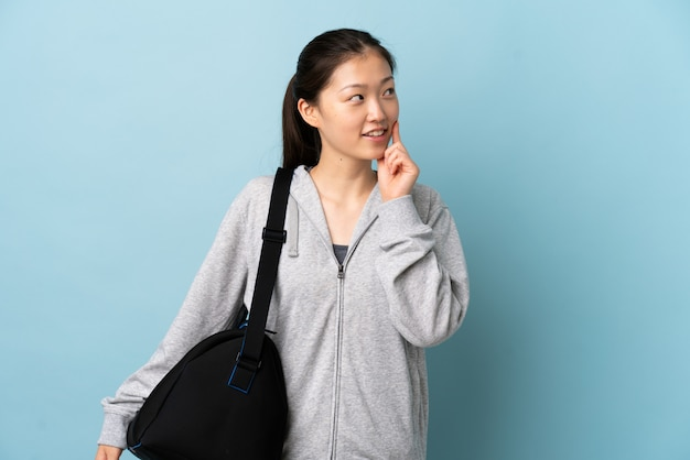 Young sport chinese  woman with sport bag over isolated blue wall thinking an idea while looking up