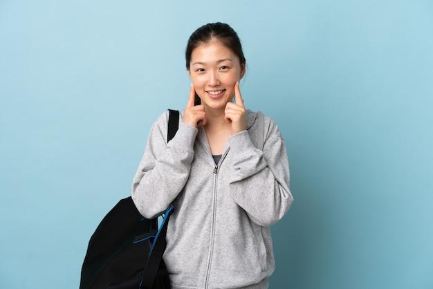 행복하고 즐거운 표정으로 웃고 고립 된 파란색에 스포츠 가방 젊은 스포츠 중국 여자