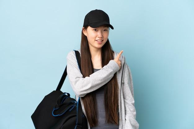 젊은 스포츠 중국 여자 블루 위에 스포츠 가방 놀라게 하 고 측면을 가리키는