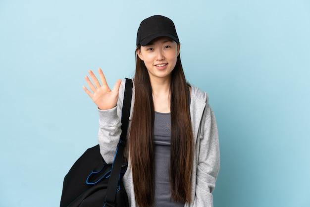 Молодая спортивная китаянка с спортивной сумкой над изолированной синей, считая пять пальцами
