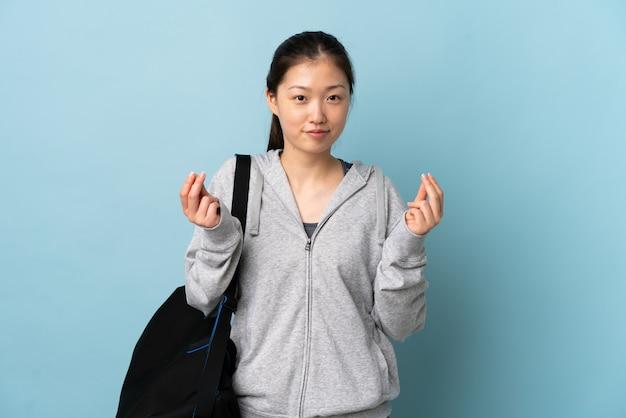 孤立した青いお金を稼ぐジェスチャーの上にスポーツバッグを持つ若いスポーツ中国人女性