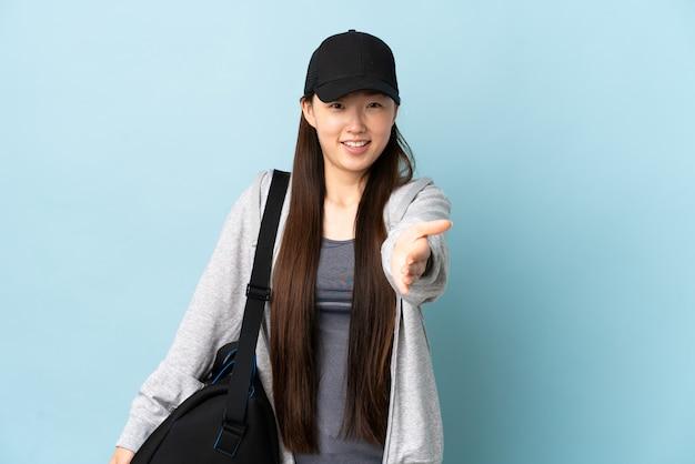 Молодая спортивная китаянка со спортивной сумкой над изолированной синей трясет рукой для заключения хорошей сделки