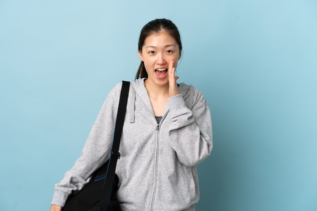 Молодая спортивная китаянка со спортивной сумкой над изолированным синим криком с широко открытым ртом