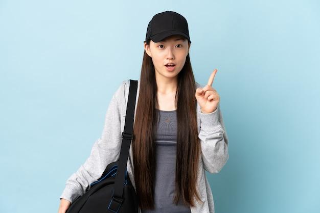 손가락을 가리키는 아이디어를 생각하는 고립 된 파란색 위에 스포츠 가방 젊은 스포츠 중국 여자