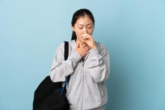 Молодая спортивная китаянка со спортивной сумкой над изолированной синей стеной много кашляет