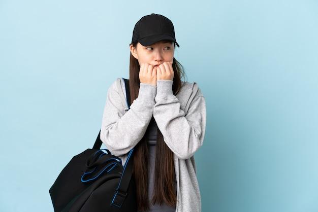 分離された青い壁にスポーツバッグを持つ若いスポーツ中国人女性神経質と怖がって手を口に入れて