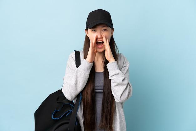 Молодая спортивная китаянка со спортивной сумкой над изолированной синей стеной кричит и что-то объявляет