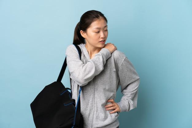 努力したために肩の痛みに苦しんでいる孤立した青い壁の上にスポーツバッグを持つ若いスポーツ中国人女性