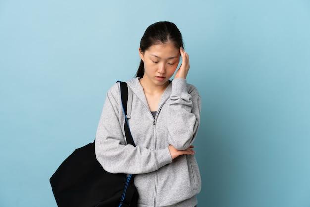 頭痛で孤立した青い壁にスポーツバッグを持つ若いスポーツ中国の女性