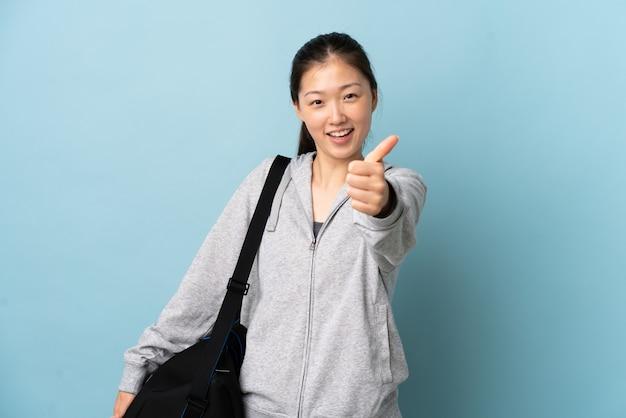 좋은 일이 일어났기 때문에 엄지 손가락으로 고립 된 파란색 벽 위에 스포츠 가방을 가진 젊은 스포츠 중국 여자