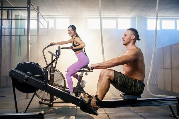 Young sport couple doing exercises on the simulators in the gym.